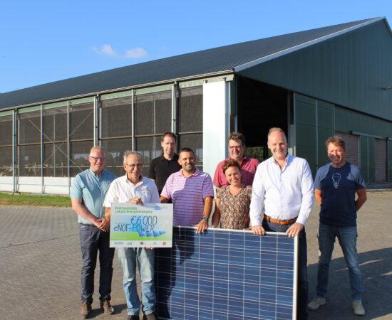 Decoratieve afbeelding van initiatiefnemers van een energiecollectief bij een zonnepaneel en een cheque