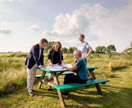 Decoratieve afbeelding van initiatiefnemers van De Landschapswerkplaats om een picknicktafel, pratend over plannen