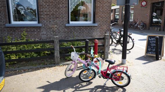 Decoratieve afbeelding van twee kinderfietsjes in Loppersum met een bord van een winkel ernaast