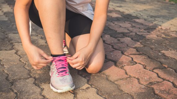 Decoratieve afbeelding van een meisje die op de grond zit om haar sportschoenen te strikken