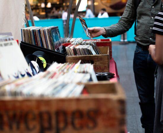 Decoratieve afbeelding van mensen die tussen vinylplaten kijken op een rommelmarkt