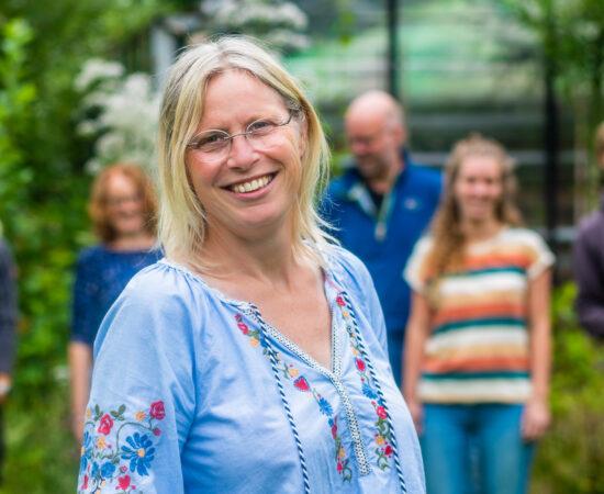 Ria Schuurman met de rest van de initiatiefnemers van het project 'Elk dorp een eigen voedseltuin' op de achtergrond