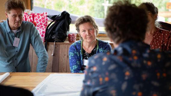 Decoratieve afbeelding van mensen die aan tafel overleggen