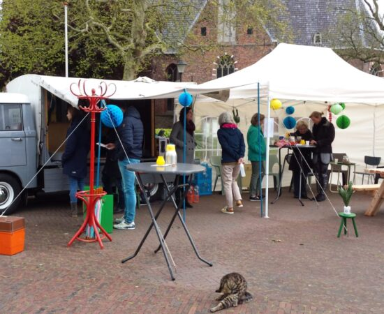 Foto van een busje en een markt waar mensen lopen om ideeën op te halen in Loppersum