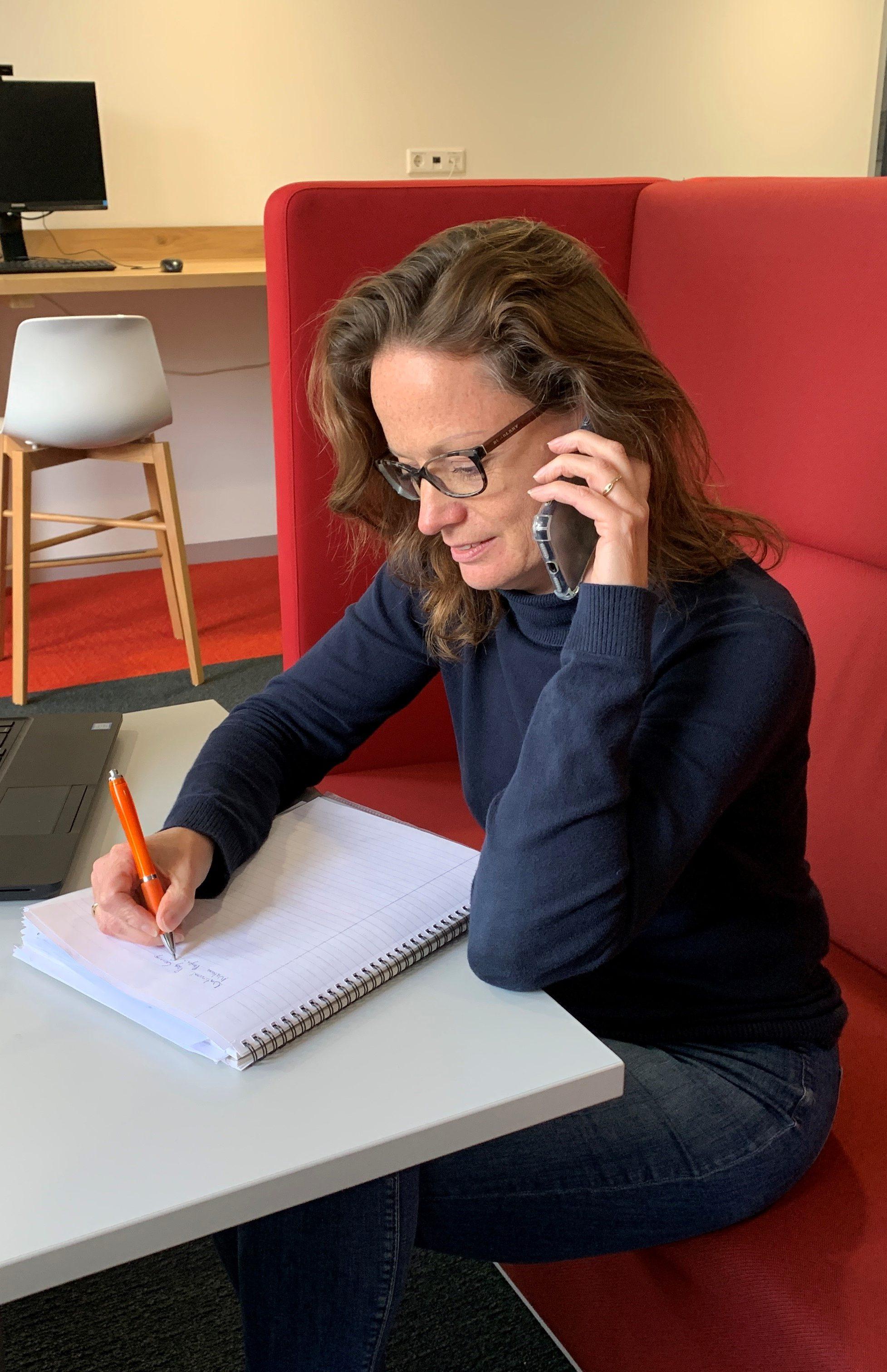 Decoratieve foto van Hetty die aan het telefoneren is en iets noteert